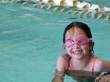 Cute kid wearing goggles in the pool.