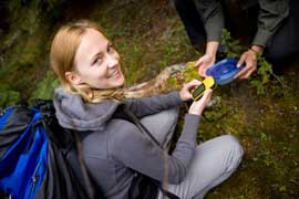 Kneeling women with GPS and geocache