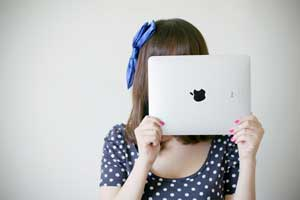 Picture of a girl holding an iPad in front of her face so you see the back of the iPad with the Apple logo.