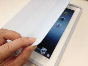 Closeup picture of an iPad with a hand opening up the cover for a little peek.